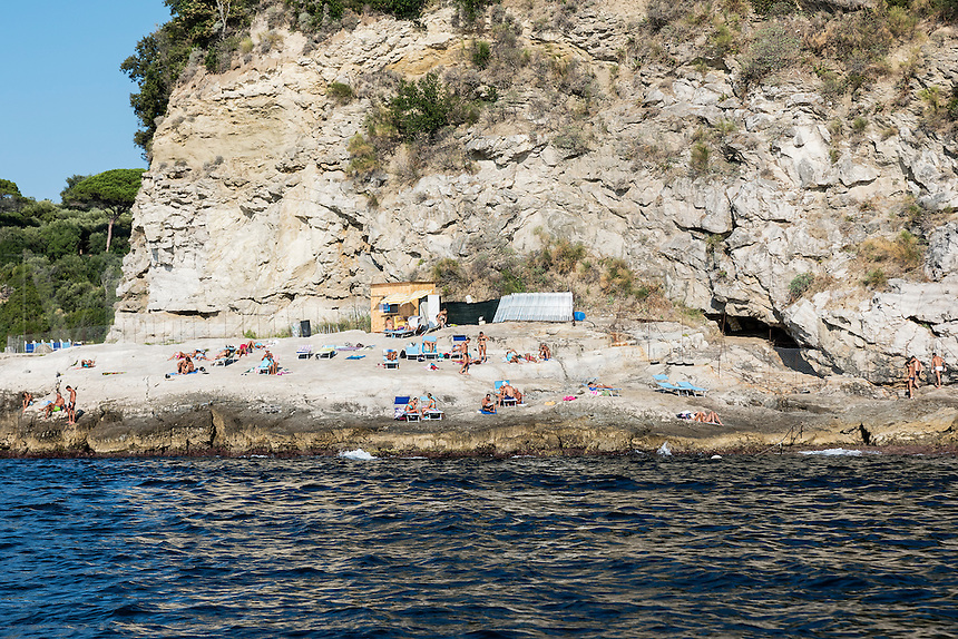 Sunbathers enjoy a rugged rock beach along the Sorrento coast, Compania, Italy