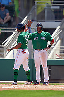 Boston Red Sox J.D. Martinez (28) high fives Xander Bogaerts (2) after scoring on a home run by Rafael Devers (not shown) during a Major League Spring Training game against the Minnesota Twins on March 17, 2021 at JetBlue Park in Fort Myers, Florida.  (Mike Janes/Four Seam Images)