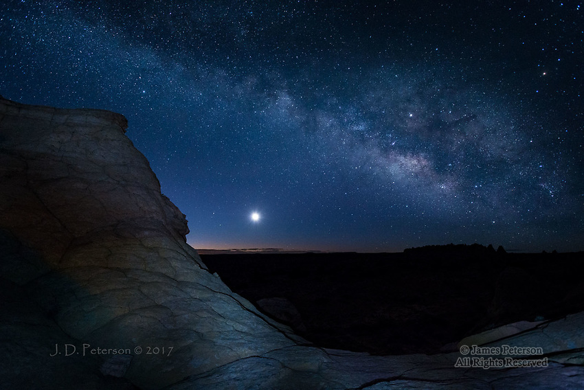 Milky Way and Moonrise, Coyote Buttes South, Arizona ©2017 James D Peterson.  This scene, in the Vermilion Cliffs National Monument, was captured before dawn in late Fabruary when a thin crescent Moon was rising beneath the Milky Way.  The Moon (even its dark side) is so much brighter than the stars that it overwhelms the ability of the camera to capture its details.  We used just a bit of light painting on the foreground ridge to reveal its texture.
