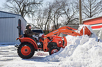 Jerry Cook, co-owner of Cook's, uses a tractor to push snow from a parking lot, Thursday, February 18, 2021 at Cook's Natural Foods Market in Rogers. Check out nwaonline.com/210219Daily/ for today's photo gallery. <br /> (NWA Democrat-Gazette/Charlie Kaijo)