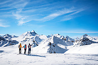 Three women looking at the alpine landscape they are entering while on a ski tour from Val d'Anniviers. Switzerland.