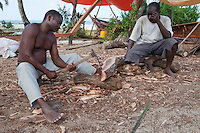 Nungwi, Zanzibar, Tanzania.  Dhow Construction, Boat Building.  Carpenter using an adze to shape the end of a log.  His companion holds it steady.