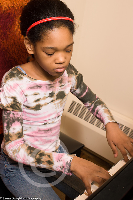 Education public school grade 3 girl playing musical instrument piano in music lesson arts enrichment vertical