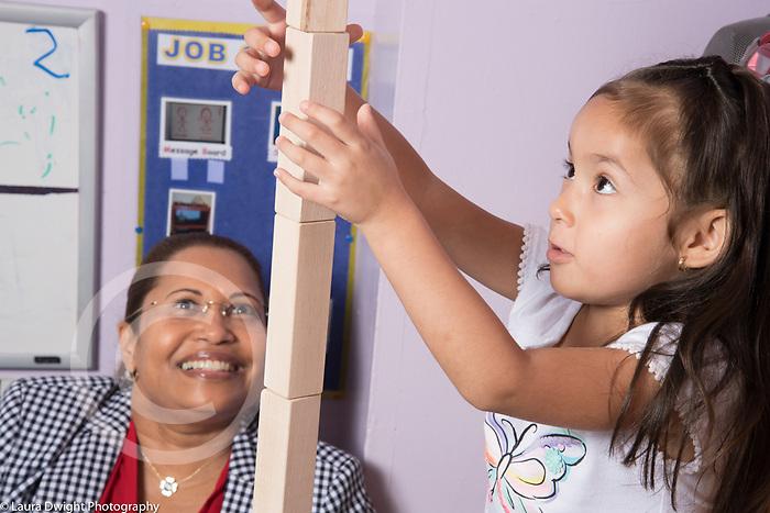 Education Preschool 3-4 year olds female teacher watching as girl builds tall block tower, smiling, encouraging