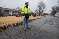 Ryan Carr, deputy director of engineering operations for the city of Springdale, points out problems with the pavement at the corner of  Shipley St. and Porter Ave. in Springdale Monday Feb. 8, 2021. (NWA Democrat-Gazette/J.T. Wampler)