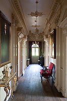 The walls of a long corridor are punctuated by pedimented doorways and hung with gilt-framed portraits