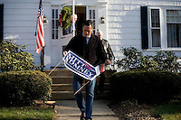 Republican presidential candidate Mitt Romney, former governor of Massachusetts, speaks with supporter James Conway at his home in Manchester, New Hampshire, on Sat. Dec. 3, 2011. The neighborhood traditionally votes Republican.  Romney spent about an hour walking through the neighborhood knocking on doors to speak with likely primary voters in the area.