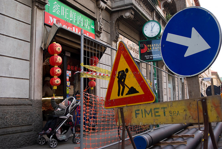 milano,  quartiere sarpi - chinatown. davanti a una macelleria cinese in via paolo sarpi, lavori per la creazione di una zona a traffico limitato (ztl) --- milan, sarpi district - chinatown. in front of a chinese butcher shop, works for the closing to traffic of paolo sarpi street