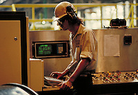Man operating computerized controls at steel fabrication plant. Birmingham Alabama, Copperweld.