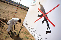 A sign saying weapons are prohibited in the Swabi Refugee camp. The camp is run by Red Cross/Red Crescent (ICRC), and currently houses around 18,000 refugees. The Pakistani government began an offensive against the Taliban in the Swat Valley in April 2009, which led to a major humanitarian crisis. Up to two million civilians were estimated to have been displaced by the fighting.