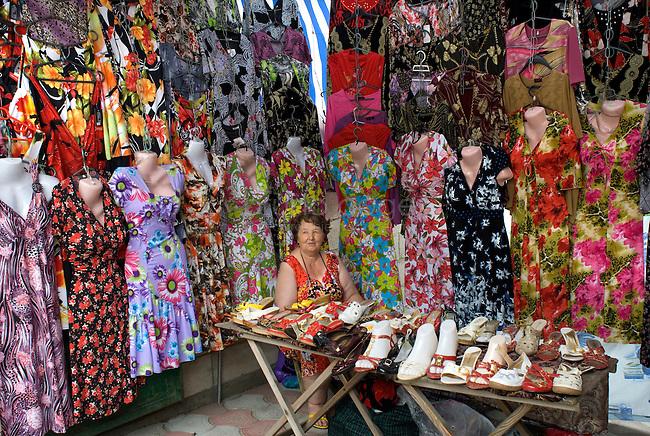 REPUBLIC OF MOLDOVA, Gagauzia, Comrat, 2009/06/26..A saleswoman of colorful dresses on the market of Comrat. Capital of Gagauzia, Comrat is the main market of the autonomous region. Each morning, tens of thousands come from all over the Gagauz region sourcing manufactured goods and clothing came directly from China..© Bruno Cogez..REPUBLIQUE MOLDAVE, Gagaouzie, Comrat, 26/06/2009..Une vendeuse de robes colorees sur le marche de Comrat. Capitale de la Gagaouzie, Comrat est le principal marche de la région autonome. Chaque matin, des dizaines de milliers de Gagaouzes viennent de toute la region s'approvisionner en produits manufactures et en vetements venus directement de Chine..© Bruno Cogez