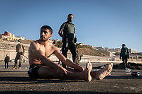 CEUTA, SPAIN ‐ MAY 19: A young migrant who has crossed the border between Spain and Morocco by swimming along the Tarajal beach, waits, guarded by the army, to be returned to Morocco on May 19, 2021 in Ceuta, Spain.  After a diplomatic conflict between Spain and Morocco, thousands of migrants who have taken advantage of the little Moroccan police activity on the border to cross it mainly by swimming, which has caused a migration crisis with the entry of more than 8000 migrants from the African country. (Photo by Joan Amengual/VIEWpress )