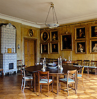 An 18th century blue and white tiled stove stands in the corner of this dining room which has marbleised walls and grained doors
