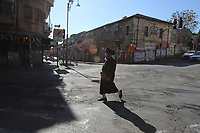 Un Haredi o temeroso de dios vistiendo un barbijo cruza la intersección mas importante del barrio ultraortodoxo Mea Shearim, conocida como Kikar Hashabat. En días normales este cruce es la zona mas atestada de gente en el barrio durante todo el día; tras el confinamiento decretado como parte de la lucha contra el COVID 19 las calles del barrio se encuentran vacías. Las autoridades israelíes declararon la ciudad  ultrareligiosa Bnei Brak y los barrios ultra ortodoxos de Jerusalén bajo sitio en un esfuerzo por controlar el contagio de la pandemia.<br /> Foto Quique Kierszenbaum