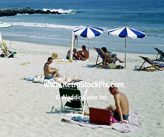 Allaire Hotel, Spring Lake, NJ. Man reading a book on the beach. His briefcase sits next to his beach chair. 1962