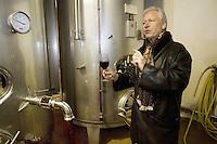 "Switzerland. Canton Ticino. Ligornetto. Luigi Zanini. Wine grower and producer. Owner of the firm ""Vinattieri Ticinesi"" . Luigi Zanini is tasting a 2007 Merlot red wine. Wineglass. Fermenting cellar for last harvested grapes. Inox tuns.  © 2008 Didier Ruef"