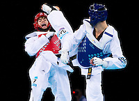 04 DEC 2011 - LONDON, GBR - Aaron Cook (GBR) (on left, in red) evades a kick from Nicolas Garcia (ESP) (on right, in blue) during their men's -80kg category semi final contest at the London International Taekwondo Invitational and 2012 Olympic Games test event at the ExCel Exhibition Centre in London, Great Britain .(PHOTO (C) NIGEL FARROW)