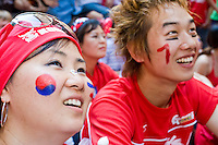 """South Korea fans gather by the hundreds to watch their team play against France on June 18, 2006 on a giant outdoor television in a section of New York City known as """"Korea Way"""".<br /> <br /> The World Cup, held every four years in different locales, is the world's pre-eminent sports tournament in the world's most popular sport, soccer (or football, as most of the world calls it).  Qualification for the World Cup is open to any country with a national team accredited by FIFA, world soccer's governing body. The first World Cup, organized by FIFA in response to the popularity of the first Olympic Games' soccer tournaments, was held in 1930 in Uruguay and was participated in by 13 nations.    <br /> <br /> As of 2010 there are 208 such teams.  The final field of the World Cup is narrowed down to 32 national teams in the three years preceding the tournament, with each region of the world allotted a specific number of spots.  <br /> <br /> The World Cup is the most widely regularly watched event in the world, with soccer teams being a source of national pride.  In most nations, the whole country is at a standstill when their team is playing in the tournament, everyone's eyes glued to their televisions or their ears to the radio, to see if their team will prevail.  While the United States in general is a conspicuous exception to the grip of World Cup fever there is one city that is a rather large exception to that rule.  In New York City, the most diverse city in a nation of immigrants, the melting pot that is America is on full display as fans of all nations gather in all possible venues to watch their teams and celebrate where they have come from."""