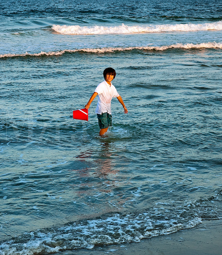 Boy playing in the ocean.