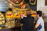 Bangkok, Thailand.  Worshipers Making Offerings to a Reclining Buddha, Wat Saket (Phu Khao Thong), the Golden Mount.