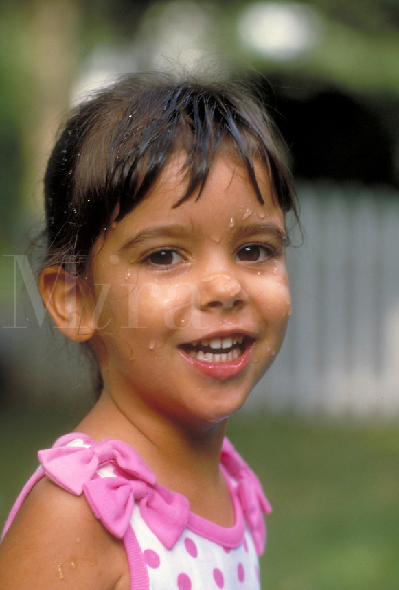 Smiling young black-haired girl with water drops on her face. New Jersey.