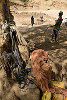 ETHIOPIA, Southern Nations, Lower Omo valley, Kangaten, village Kakuta, Nyangatom tribe, shepherds give water to their goats from water holes at dry river Kibish, shepherds carry machine gun to protect themselves from cattle raids of Turkana tribe, Heckler and Koch automatic machine gun G3 serial No. G3 CO F 00977 / AETHIOPIEN, Omo Tal, Kangaten, Dorf Kakuta, Nyangatom Hirtenvolk, Hirten tragen Waffen zum Schutz vor Viehdiebstaehlen durch Turkana Voelker, Heckler und Koch Sturmgewehr G3 serial No. G3 CO F 00977