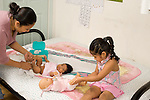 modeling imitation child development 3 year old girl plays with doll as mother changes diaper of newborn baby sister horizontal Hispanic Mexican American EVOstock