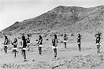 A troupe of young female Majorettes line up before moving off desert landscape Calico California USA 1971 .