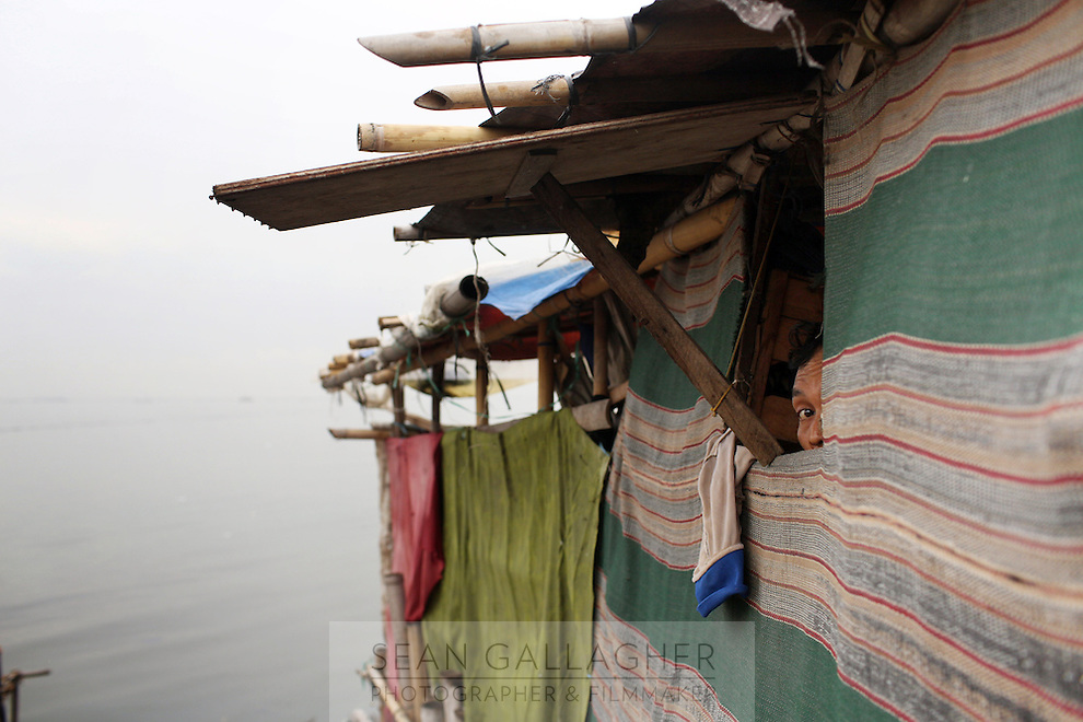 """A resident of a fishing community looks out from his home on the shores of Jakarta's bay. According to the the Climate Reality Project, """"without flood protection measures, sea level rise could expose up to 6 million Indonesians to annual coastal flooding. The worst of the flooding would occur on the island of Java, where Jakarta is located."""""""