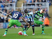 Papiss Cisse of Newcastle United (centre) fends off Angel Rangel of Swansea City (right) during the Barclays Premier League match between Newcastle United and Swansea City played at St. James' Park, Newcastle upon Tyne, on the 16th April 2016