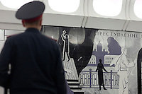 "Moscow, Russia, 20/06/2010..A policeman looks at murals depicting Raskolnikov's double murder and Svidrigailov's suicide in Crime & Punishment at the just-opened Dostoevsky metro station, the newest in Moscow's underground metro system. The station's opening was delayed by several weeks after psychiatrists claimed the gloomy and violent images in murals depicting scenes from Dostoevsky's novels would make the station a ""mecca for suicides""."