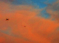 UFO and airplane; alien craft at far left/faceted-angled design with distinct edges.  Hover w/ slight rocking motion.  Airliner much smaller and SW of UFO object.