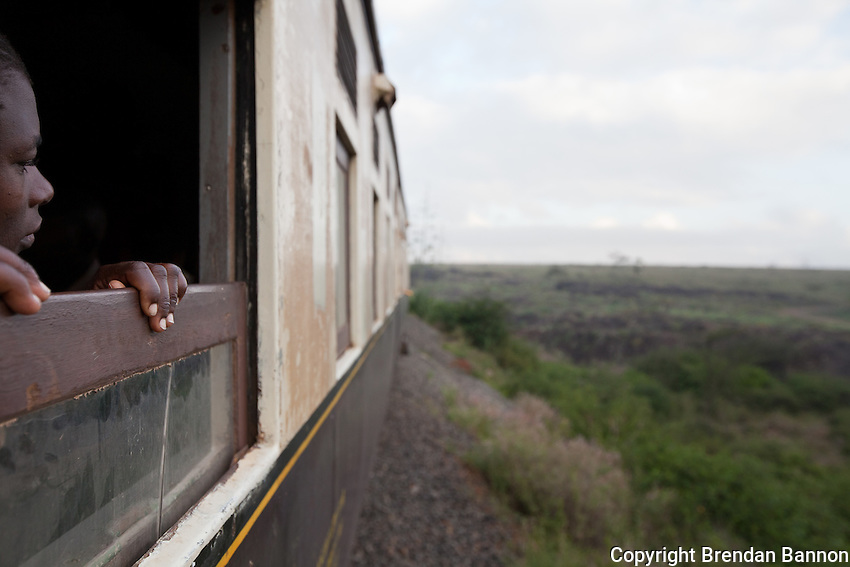 A passenger enrout to Nairobi from Athi River watching the landscape roll by. The commuter train service was launched in March of 2011.