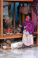 India, Rishikesh.  Woman Warming her Hands in the Morning Cold.