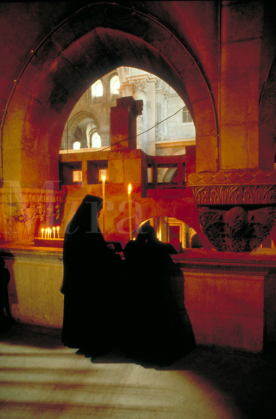 Two worshippers, one stands while the other kneels at a Holy Sepulcher in a Christian church in Jerusalem. People. two worshippers. Jerusalem, Israel.
