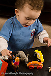 2 year old toddler boy at home playing with human people figures and vehicles vocalizing language development vertical