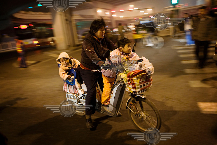 A family travel home in the evening on a small motorbike.