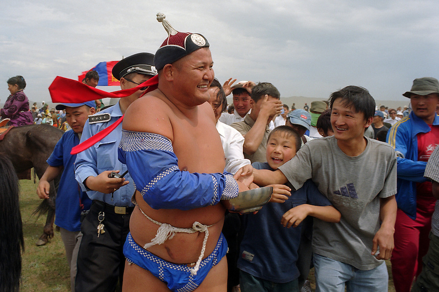 Khui Doloon Khudag, Mongolia, July 2003..Competitors and spectators at the Mongolian Wrestling contests in the national Naadam. Winning wrestlers are national heroes & are mobbed as they leave the field.