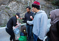 Pictured: Migrants are given food on the motorway Thursday 25 February 2016<br />Re: Hundreds of migrants, including families with young children, that were stranded at Tempe in central Greece, were forced to walk on foot on the motorway to reach Idomen, about 168 kilometres away, in the northern part of the country, at the Greek FYRO Macedonian border. Local police were at first escorting them, then made sure that they were safely transported on coaches.