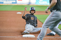 Domingo Santana (13) of the Fresno Grizzlies  slides into third base in action against the Salt Lake Bees in Pacific Coast League action at Smith's Ballpark on June 13, 2015 in Salt Lake City, Utah.  (Stephen Smith/Four Seam Images)