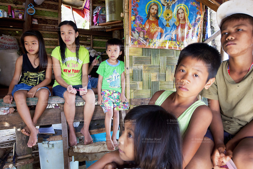 Philippines. Province Eastern Samar. Hernani. Barangay (neighbourhood) Carmel. Traditional hut. Rowina Calvadares (13 years old, wearing a green New York t-shirt) with her sister Rica (left, 11 years) and brother Ric (right, 7 years) are seated on the floor of their one room house. Two other brothers and a small sister are also in the house. The boy and girls are orphans. A religious catholic poster with Jesus and the Virgin Mary is on the wall. The roof and the walls of their house were damaged by typhoon Haiyan's winds. Typhoon Haiyan, known as Typhoon Yolanda in the Philippines, was an exceptionally powerful tropical cyclone that devastated the Philippines. Haiyan is also the strongest storm recorded at landfall in terms of wind speed. Typhoon Haiyan's casualties and destructions occured during a powerful storm surge, an offshore rise of water associated with a low pressure weather system. Storm surges are caused primarily by high winds pushing on the ocean's surface. The wind causes the water to pile up higher than the ordinary sea level. 25.11.13 © 2013 Didier Ruef