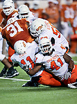 Texas Longhorns running back Cody Johnson (31) gets tackled by Oklahoma State Cowboys linebacker Shaun Lewis (11) and Oklahoma State Cowboys defensive end Jamie Blatnick (50) during the game between the Oklahoma State Cowboys and the University of Texas in Austin Texas Longhorns at the Daryl K. Royal- Texas Memorial Stadium in Austin, Texas. The Oklahoma State Cowboys defeated the Texas Longhorns 33 to 16.