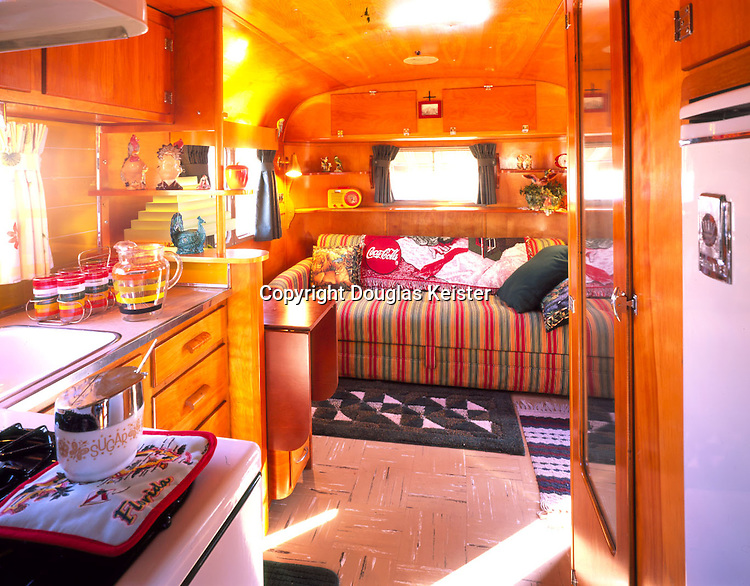Vagabond interior: The interior of the Vagabond is a fine example of tidy and efficient design. The warm wood surfaces combined with period accessories work perfectly to give the trailer the look and feel of a cozy summer cottage.