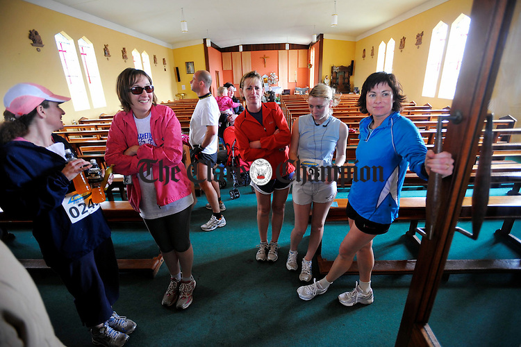 Athletes and supporters take refuge from the pouring rain inside Kilnaboy church  at the Sonny Murphy memorial 10k road race in Kilnaboy. Photograph by John Kelly.