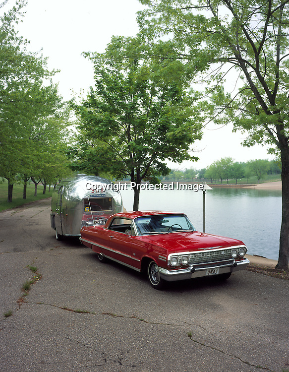 1963 red Chevrolet Impala SS pulling a silver 1963 Bambi Airstream.