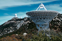The Kitt Peak National Observatory structures - the Mayall Telescope is housed in the tallest structure (upper left). A large radio antennae is in the foreground. Arizona.