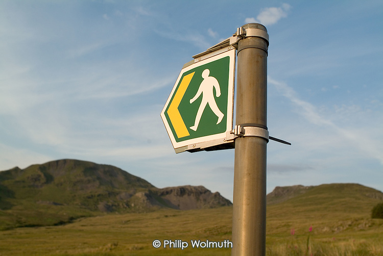 Footpath sign in evening light below Moelwyn Mawr and Moelwyn Bach in the Snowdonia National Park in North Wales