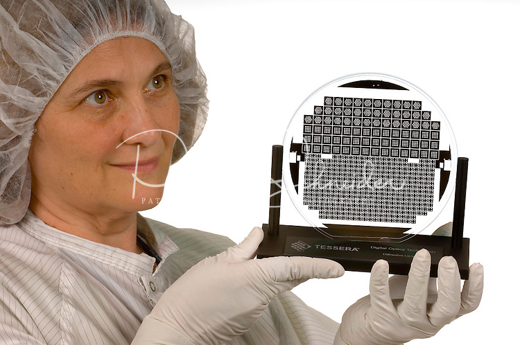 An employee of Tessera's Charlotte, NC, operations displays a sample of the digital optics applications the company produces via clean room manufacturing . The imaging and optics company makes wafer-level optics, image sensor packaging and ?smart? image enhancement technologies, and micro-optic solutions.