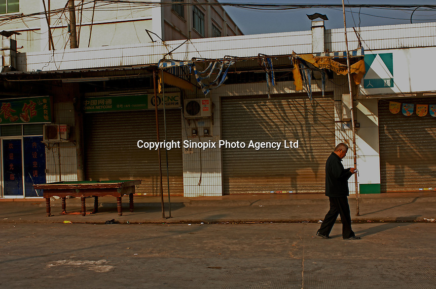 An old man passes a stree of closed shops, Dingfu Factory in Houjie Town, Dongguan, China. As the economy changes and Chinese labour gets more expensive, factories are closing leaving ghost towns behind them..20 Dec 2007