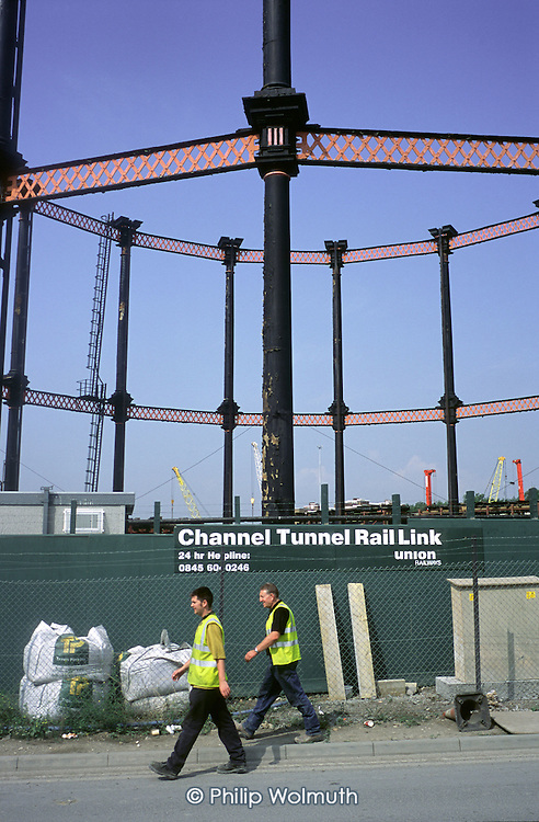 London building workers walk by a landmark Victorian gas holder in Kings Cross during work on the Channel Tunnel Rail Link.